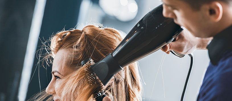 Blonde woman having her hair blow-dried by a male hair stylist.